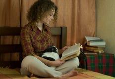 Girl and a cat reading an open book Stock Photos