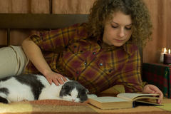 Girl and a cat reading an open book Royalty Free Stock Photos