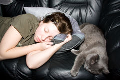 Girl and cat a sleep. Girl with her cat sleeping in the sofa Royalty Free Stock Photo
