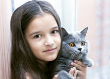 Girl with a cat smiling in the morning at the window Stock Photography