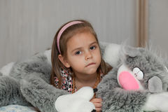 Girl with cat soft toy. Little girl in the embraces of cat soft toy Royalty Free Stock Photography