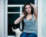 Girl and a cat on the window. Girl in a vest and a cat sitting on the window royalty free stock photos