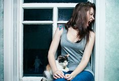 Girl and a cat on the window. Girl in a vest and a cat sitting on the window stock photography