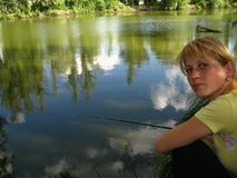 Girl catches a fish. The water reflections, summer sky and trees stock photos