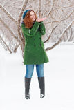 Girl catches snow by palms outdoor at winter day Stock Image