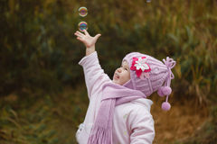 The girl catches soap bubbles in autumn Royalty Free Stock Image