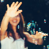 Girl catching bubbles Stock Photos