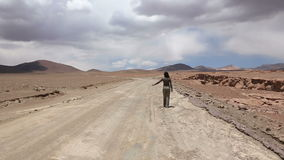Girl catching the car. Woman catches the car at deserted road on sunny day, Bolivia stock video