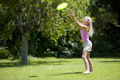 Girl (8-10) catching flying disc outdoors Royalty Free Stock Photos