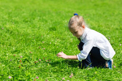 Girl catching a grasshopper Royalty Free Stock Photos