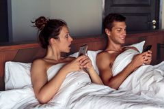 Jealous woman spying her husband mobile phone in bedroom royalty free stock image
