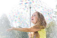 Girl catching raindrops Stock Images