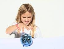 Girl catching saving pig full of money Royalty Free Stock Images
