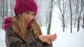 Girl catching snowflakes. At the winter park stock video footage