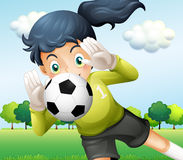 A girl catching a soccer ball Stock Photography