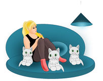 Girl with Cats. A girl sitting in a blue sofa with three cats Stock Images