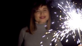 Girl of Caucasian appearance with a smile on his face holding in his hands a Sparkler.  stock video footage