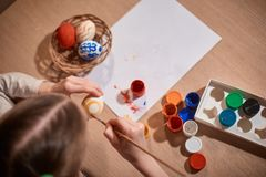 Girl Caucasian appearance with two pigtails sitting at a large wooden table and paints a brush and eggs for Easter stock photos