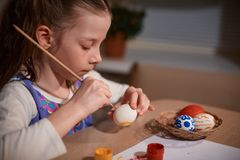 Girl Caucasian appearance with two pigtails sitting at a large wooden table and paints a brush and eggs for Easter stock images