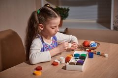 Girl Caucasian appearance with two pigtails sitting at a large wooden table and paints a brush and eggs for Easter royalty free stock images