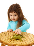 Girl cautiously stroking a toy lizard Royalty Free Stock Image