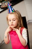 Girl celebrating birthday. Young girl in party hat celebrating her fifth birthday Stock Photos
