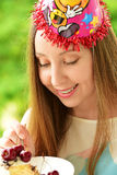 Girl in a celebratory cap. Birthday. Girl eating cake. Funny girl smiling Stock Photos