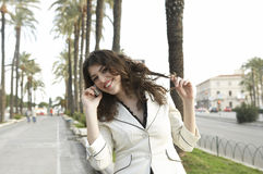 Girl with Cell and Palm Trees Stock Photography