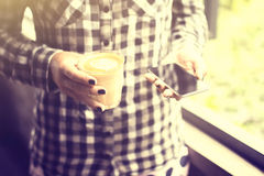 Girl with cell phone and coffee, vintage photo effect Royalty Free Stock Photos