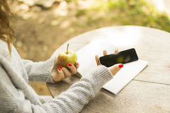 Girl with cell phone, diary and green apple Royalty Free Stock Image