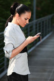Girl with cell phone mobile. Attractive business woman is typing some input into her cell phone Royalty Free Stock Image
