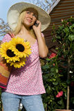 Girl On Cell Phone With Sun Hat & Sunflowers. A beautiful young blond woman wearing a sun hat talking on her cell phone while carrying a shopping bag of Stock Images