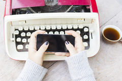 Girl with cell phone and typewriter Royalty Free Stock Photo