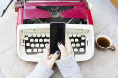 Girl with cell phone and typewriter Royalty Free Stock Image