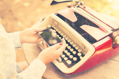 Girl with cell phone and typewriter Royalty Free Stock Photography