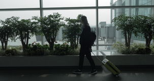 Girl with cell and suitcase walking by the window of airport terminal stock footage