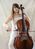 Girl with cello. Portrait of girl with a cello in studio stock image