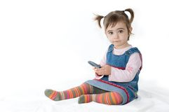 Girl and cellphone. Kid playing with a cellphone in white background Stock Photos