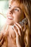 Girl with cellphone. Young woman smiling and keeping mobile phone Stock Photography
