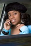 Girl with cellphone. Portrait of Flirty African-American in the car with mobile phone Stock Photo
