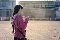 Girl with the cellphone in the beach. Teenager walking in the beach with her cellphone in hands  in Mar del Plata, Argentina Royalty Free Stock Photography