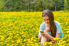 Girl with cellphone in park Royalty Free Stock Photos