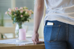 Girl with cellular phone in back pocket. Close-up of a girl in white t-shirt and blue jeans with a cellular or mobile phone in her back pocket Stock Photos
