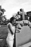 Girl in a cemetery. Remembering a lost Royalty Free Stock Photography
