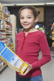 Girl With Cereal Packet In Supermarket Stock Image
