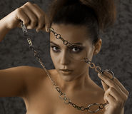 Girl with a chain. Young beautiful woman holding jewelry Stock Photos