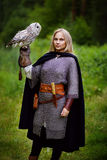 Girl in chain mail holding owl in forest Stock Image