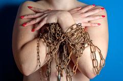 Girl with chains and padlock. On blue background upper body stock image