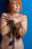 Girl with chains and padlock. On blue background upper body royalty free stock images