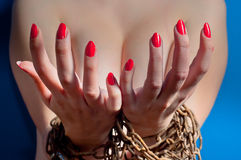 Girl with chains and red nails. Girl with chains and padlock on blue background upper body showing nails stock photography